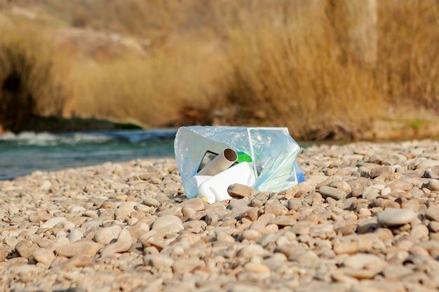 Inquinamento del fiume vicino alla riva, spazzatura vicino al fiume, rifiuti alimentari di plastica, che contribuiscono all'inquinamento.