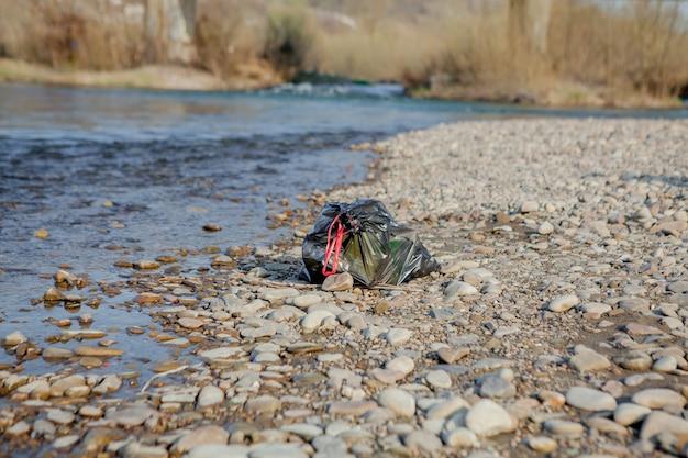 Inquinamento del fiume vicino alla riva, sacco della spazzatura vicino al fiume, rifiuti alimentari di plastica, che contribuiscono all'inquinamento.