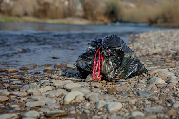 Inquinamento del fiume vicino alla riva, sacco della spazzatura vicino al fiume, rifiuti alimentari in plastica