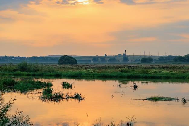 Fiume al tramonto contro il drammatico cielo arancione. paesaggio fluviale in serata estiva