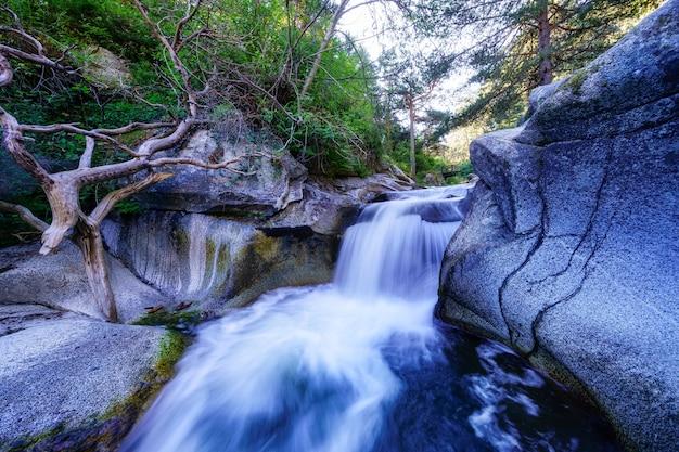 Cascata del fiume tra rocce e vegetazione verde all'alba. navacerrada.
