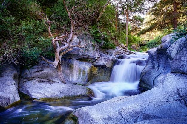 Cascata del fiume tra rocce all'alba e ponte di legno sullo sfondo. navacerrada.