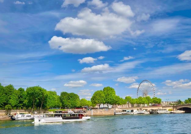 Riva del fiume a parigi con la ruota panoramica sul concorde e la nave passeggeri