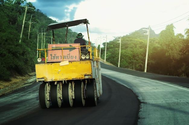Macchine per la costruzione di strade operai di manutenzione stradale con cartelli che indicano deviazione indiretta