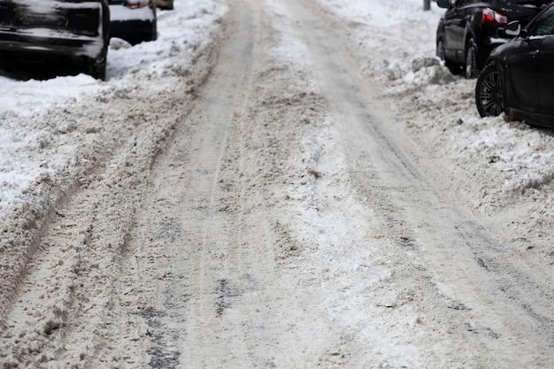 Strada coperta di neve con auto sul lato della strada. foto di alta qualità