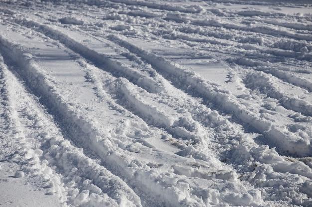 Strada coperta di neve con tracce di pneumatici per auto. foto di alta qualità