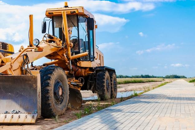 Livellatrice stradale - attrezzatura pesante per la costruzione di strade e movimenti di terra. livellamento e miglioramento della superficie del terreno. costruzione di strade e comunicazioni di trasporto.