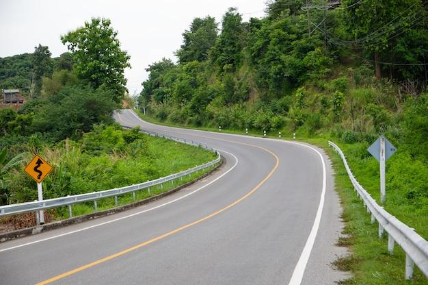 La strada è fiancheggiata da alberi e curve incantevoli.