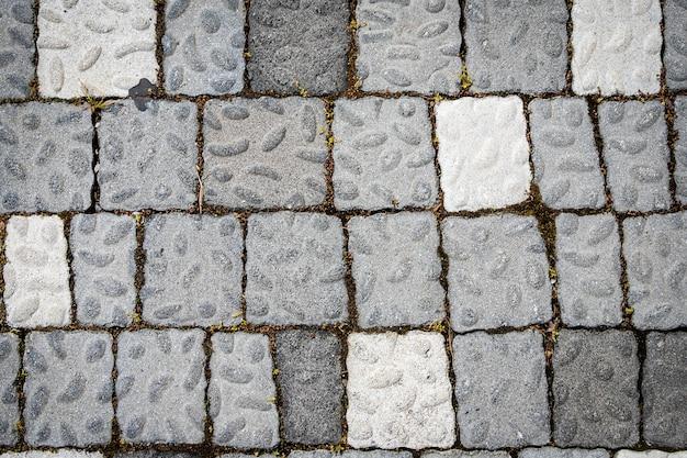 La strada è lastricata di pietre grigie, vista dall'alto. struttura in pietra, piastrelle in pietra per esterni