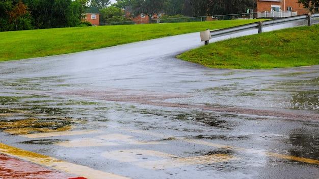 L'acqua piovana della strada cade il fondo con la riflessione del cielo blu ed i cerchi dell'acqua su asfalto scuro. previsione pioggia.