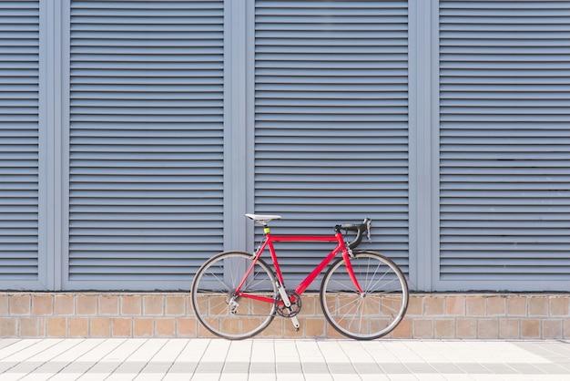 La bici rossa della strada sta su una parete grigia