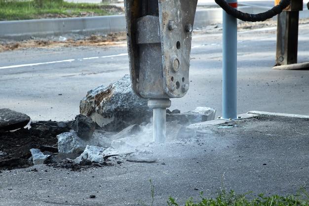 Riparazione stradale. rimozione di un vecchio strato di asfalto con martello idraulico. ricostruzione del marciapiede.