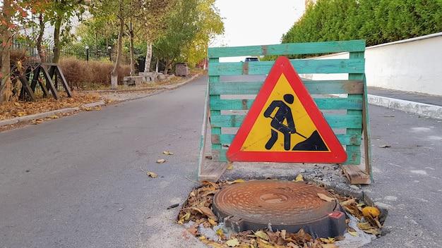 Riparazione stradale. pozzetto fognario sulla carreggiata. gli automobilisti d'avvertimento triangolare firmano con un uomo con una vanga gialla con il rosso. uomini al lavoro. segnali stradali, restrizioni di viaggio.
