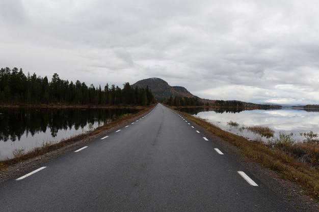 La strada che costeggia il lago al tramonto va in montagna.