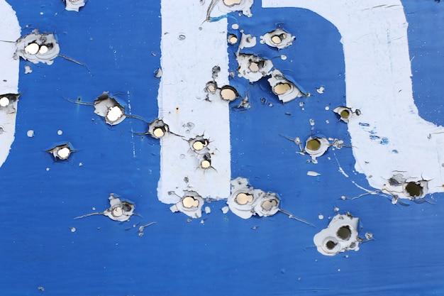Il cartello stradale del villaggio, al posto delle ostilità. fori di proiettile in metallo.