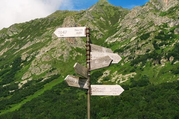 Cartello stradale con nomi di monte e destinazione in russo e inglese su tavole di legno