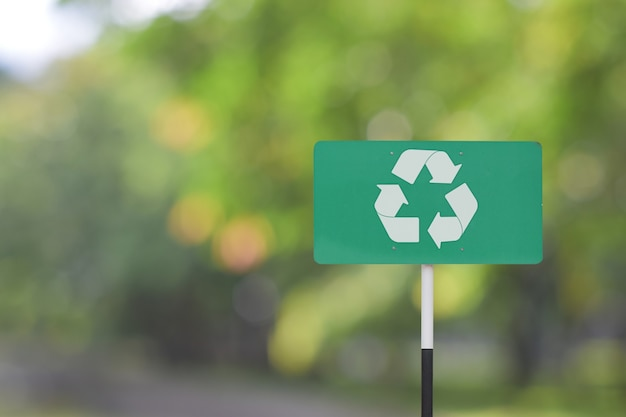 Cartello stradale con il simbolo del logo di riciclo su sfondo verde sfocatura.