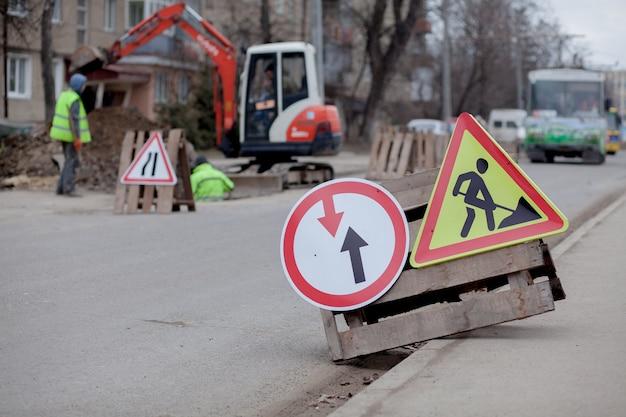 Segnaletica stradale, deviazione, riparazione stradale in strada, buca di scavo di camion ed escavatori.