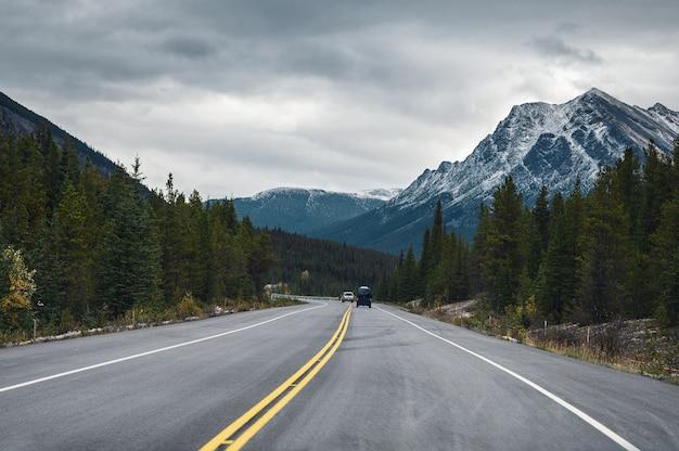 Viaggio stradale con le montagne rocciose nella foresta di autunno su tenebroso al parco nazionale di banff