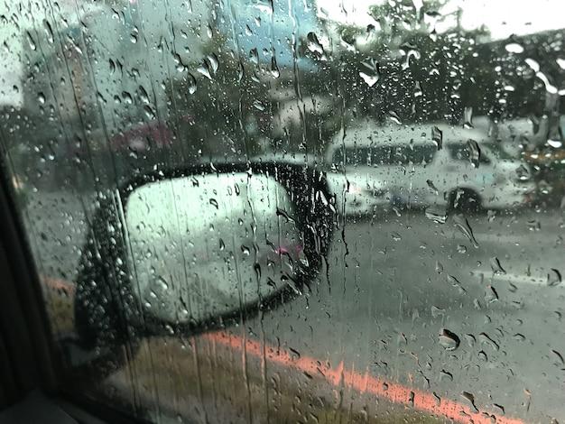 Vista della strada attraverso auto guida in gocce di pioggia