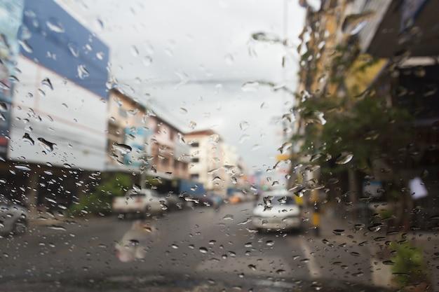Vista della strada attraverso il finestrino della macchina con gocce di pioggia