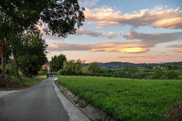 Strada con i viaggiatori in campagna incredibili nuvole colorate sopra il campo irun paesi baschi in spagna