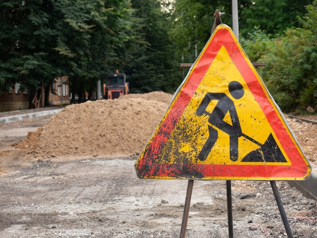 Cartello di lavori stradali sullo sfondo di una strada in costruzione
