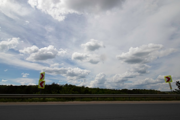 Ciglio della strada e bel cielo nuvoloso in movimento dal finestrino dell'auto