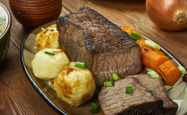 Arrosto di manzo con patate arrosto e salsa, cucina inglese, gran bretagna piatti tradizionali assortiti, vista dall'alto.