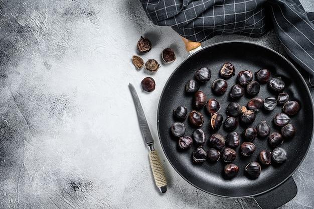 Castagne arrostite in padella su un tavolo di legno.