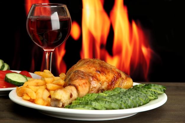 Pollo arrosto con patatine fritte e cetrioli, bicchiere di vino sul tavolo di legno sul muro di fuoco
