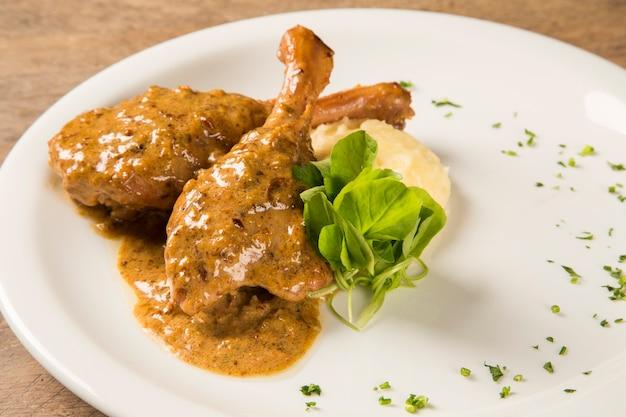 Anatra arrosto con purè di patate sul piatto.