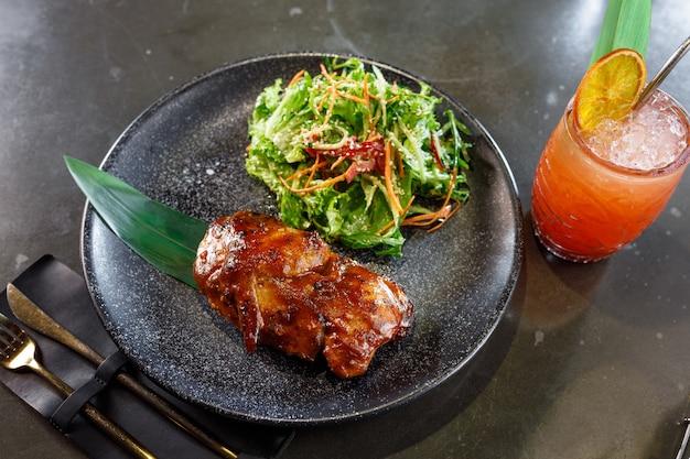 Anatra arrosto con insalata su un piatto nero