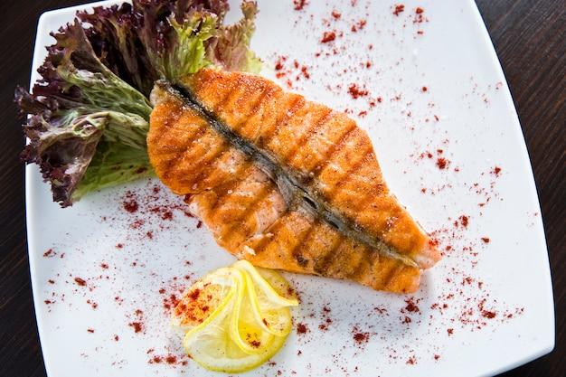 Salmone arrosto e formaggi a pasta molle su verde sopra bianco