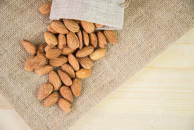 Mandorla arrostita nella borsa di tela o borsa del sacco sul fondo del sacco. la mandorla è uno spuntino o crudo di cuoco. cibo salutare. basso contenuto calorico o dieta alimentare.