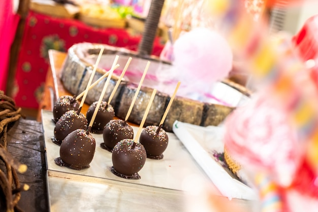 Mele arrostite immerse nel cioccolato ad una fiera.