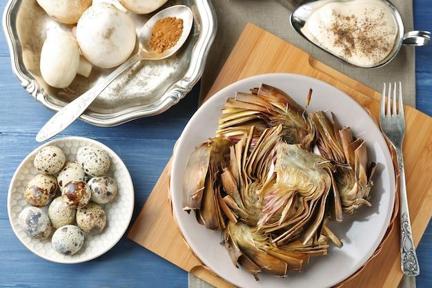 Carciofi arrostiti sul piatto, su fondo di legno di colore