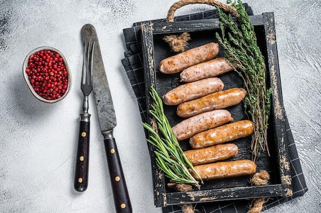 Salsicce bratwurst hot dog arrosto in un vassoio di legno con erbe aromatiche. sfondo bianco. vista dall'alto.