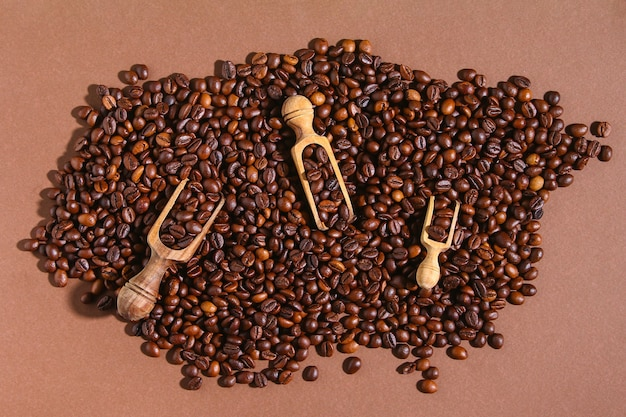 Chicchi di caffè marroni arrostiti su una priorità bassa marrone