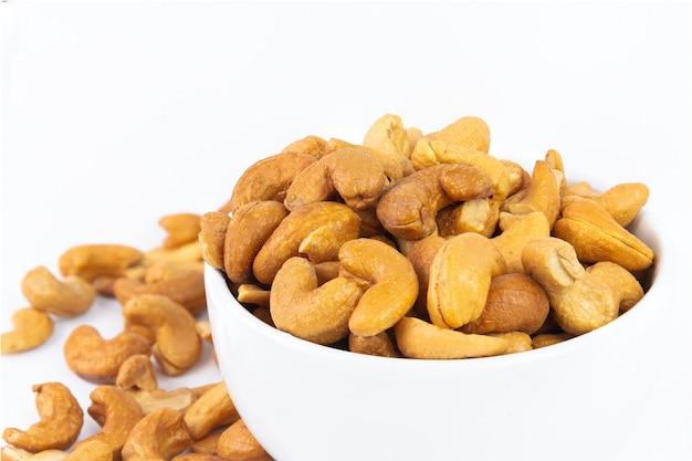 Anacardio arrostito nella ciotola bianca su bianco. l'anacardio è uno spuntino o crudo del cuoco. cibo salutare. basso contenuto calorico o dieta alimentare. anacardio con copyspace.