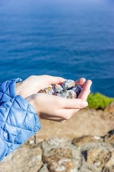 Castagne arrostite in mani femminili su sfondo blu del mare, copia dello spazio