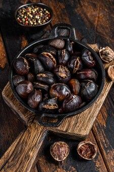 Castagne arrostite servite in padella su un tagliere di legno.