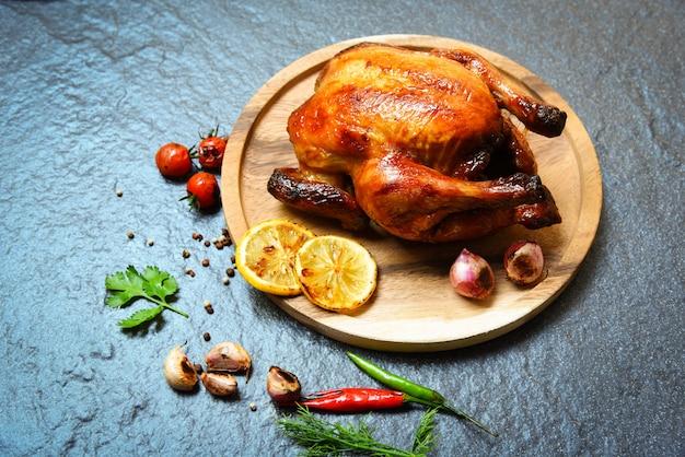 Intero pollo al forno con pollo arrostito grigliato con erbe e spezie sul piatto di legno e buio