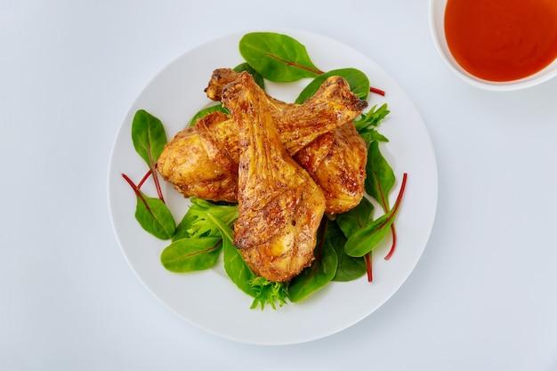 Cosce di pollo arrosto con salsa piccante su sfondo bianco. vista dall'alto.