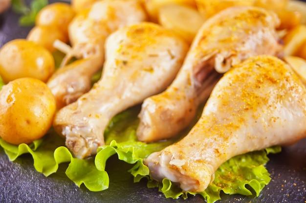 Cosce di pollo arrosto con patate, spezie ed erbe aromatiche.