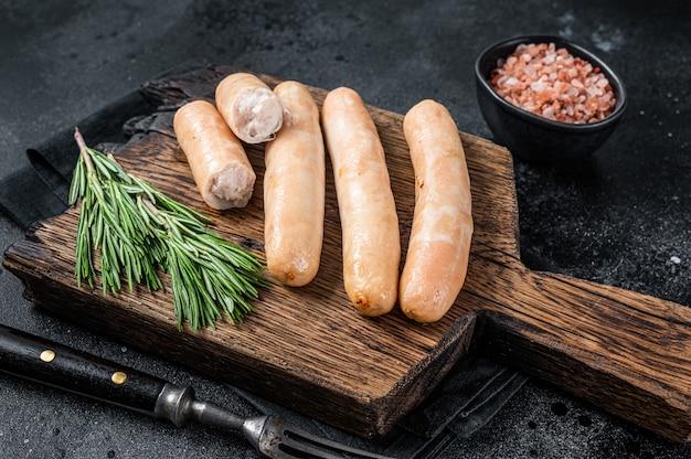 Salsicce di pollo e tacchino arrosto su una tavola di legno. sfondo nero. vista dall'alto.