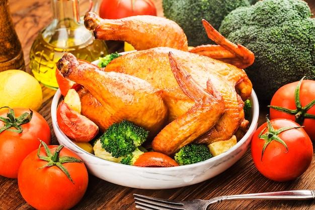 Pollo arrosto e verdure sulla tavola di legno
