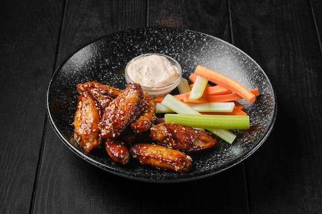 Alette di pollo arrosto, bastoncini di sedano e carota e salsa su un piatto