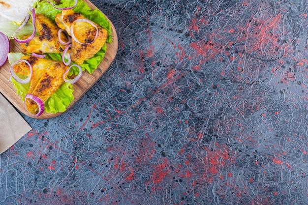 Ali di pollo arrosto con verdure sul tagliere di legno.