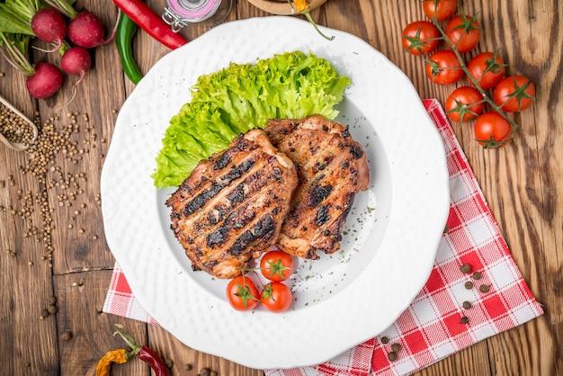 Pollo arrosto con erbe aromatiche servito su un piatto di verdure e uva